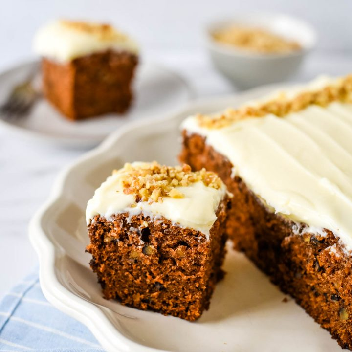 piece of carrot cake on platter with cake