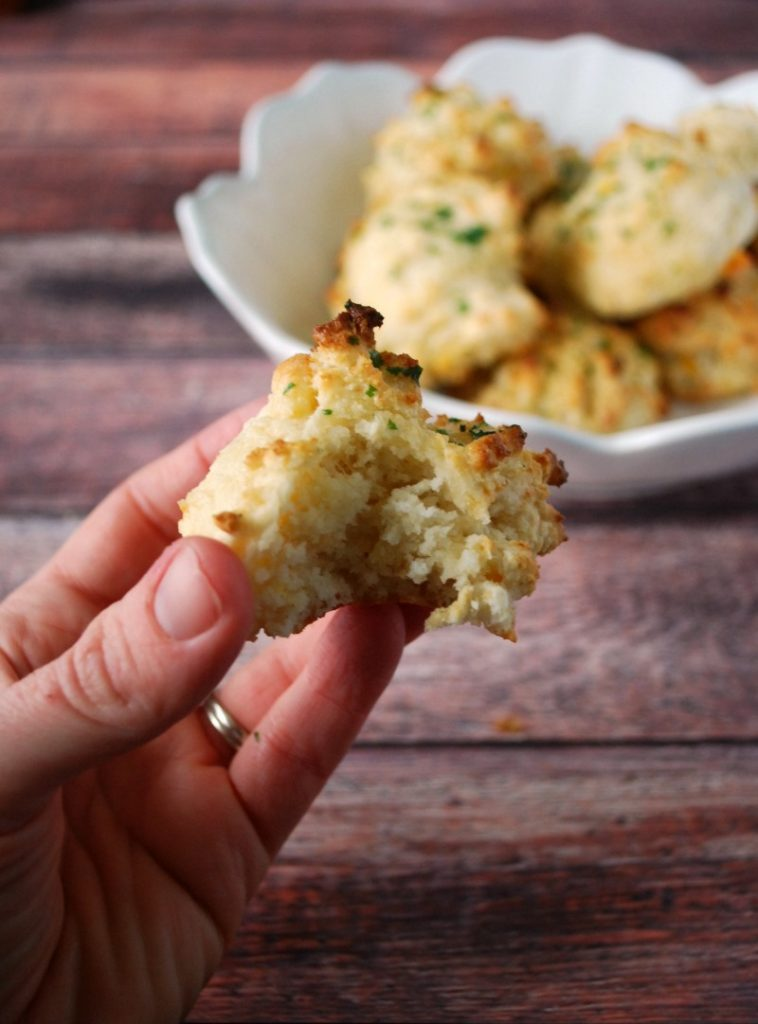 Easy Drop Cheddar Biscuit held in hand with bite taken out