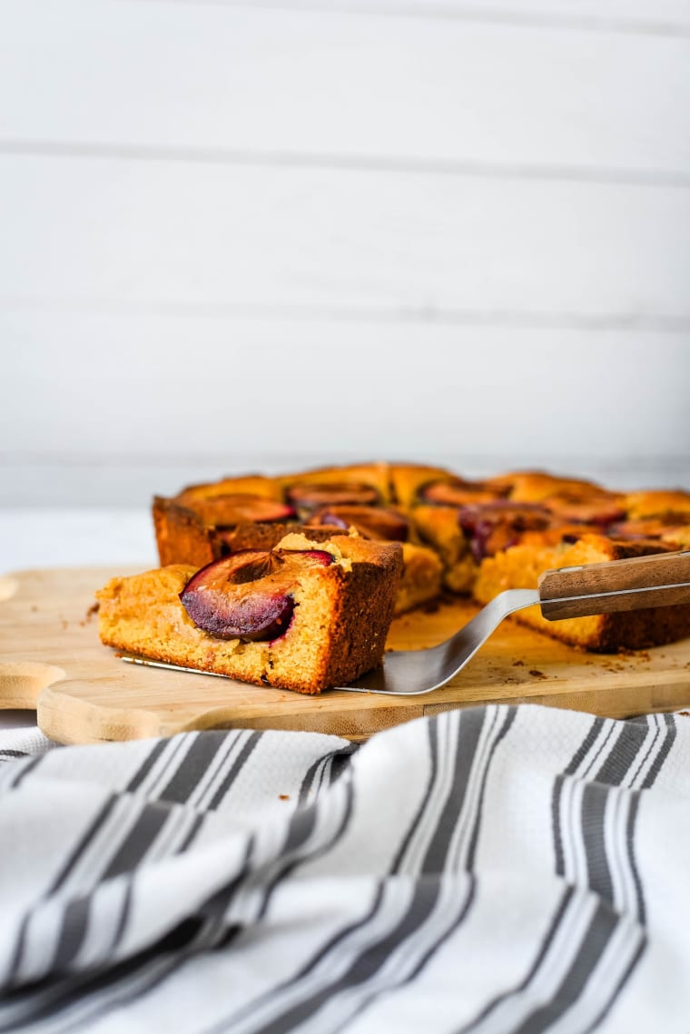spiced plum cake being served with spatula