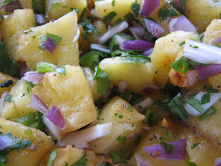A close up of a bowl of pineapple salsa with red onions and cilantro