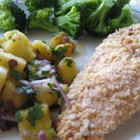 A plate of food with broccoli, chicken and pineapple salsa
