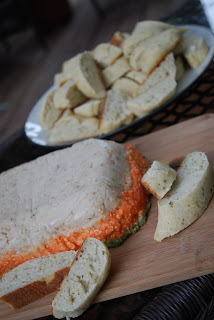 a close up of vegetable pate on cutting board with bread beside