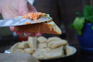 A close up of a person holding a piece of bread and spreading vegetable pate on with knife