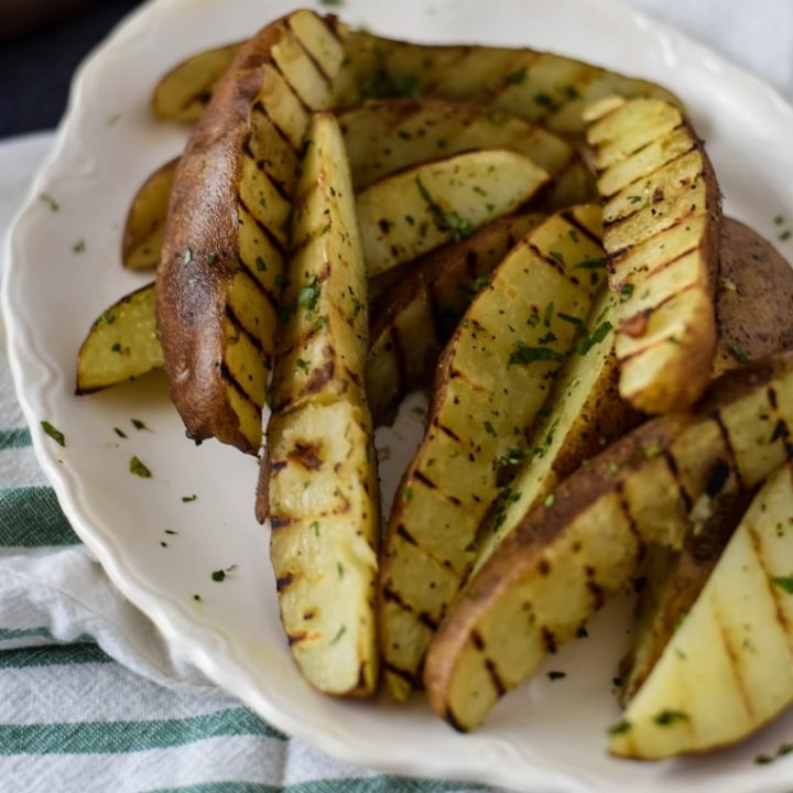 grilled potato wedges on white platter