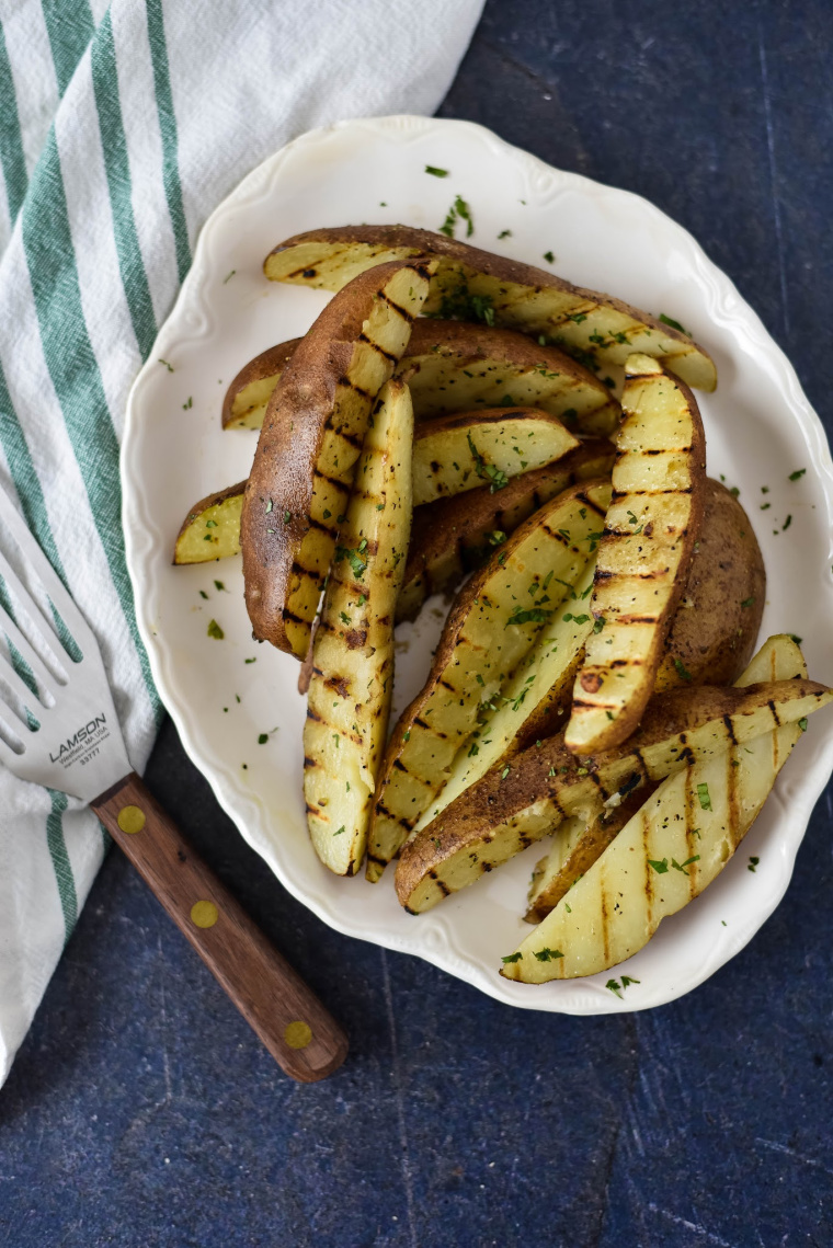 A plate of food on a table, with grilled Potato wedges and serving spatula beside