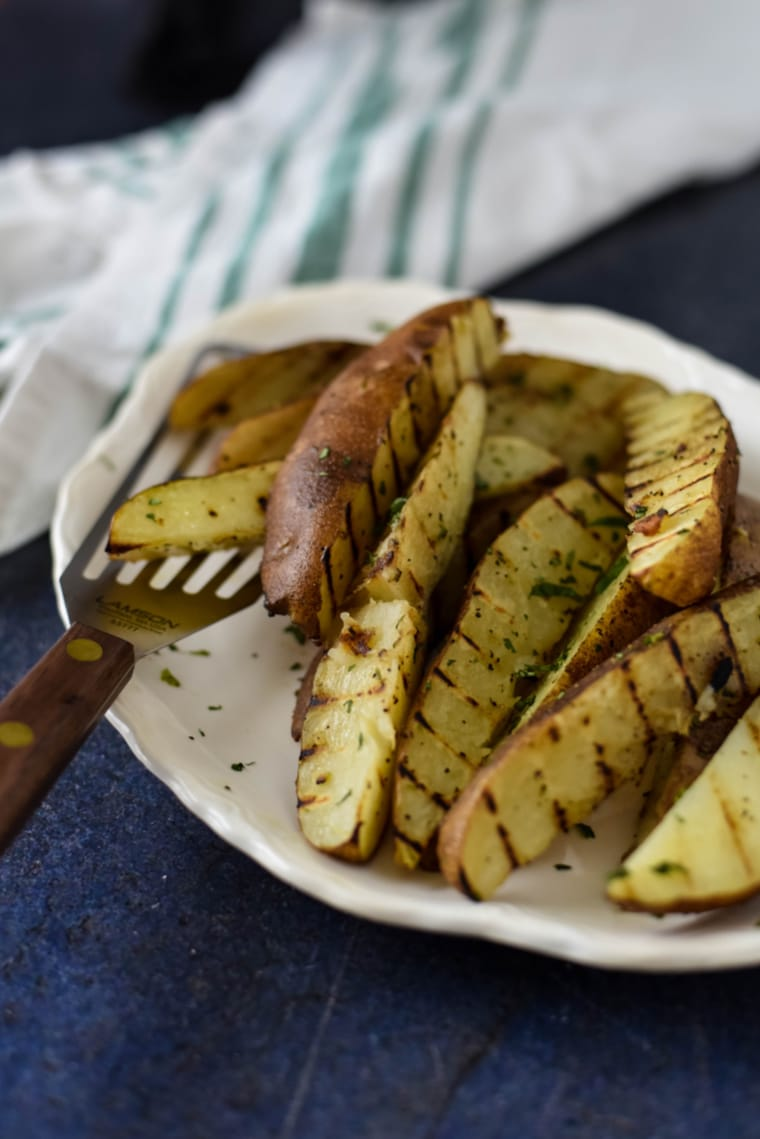 grilled potato wedges on white platter with serving utensil