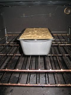 a bread tin in the oven filled with banana bread batter