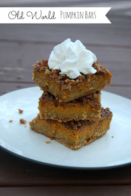 a stack of three pumpkin bars on a plate with whipped cream on the top