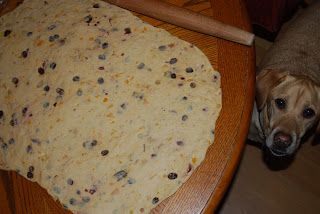 yeasted stollen dough rolled out on table with rolling pin beside