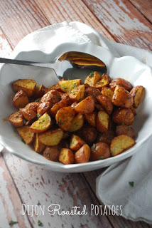 white bowl with dijon roasted potatoes and serving spoon