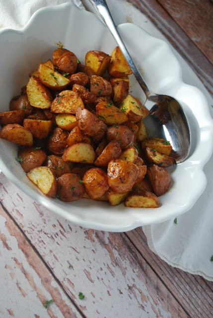 roasted potatoes in white bowl with white cloth on white wood.