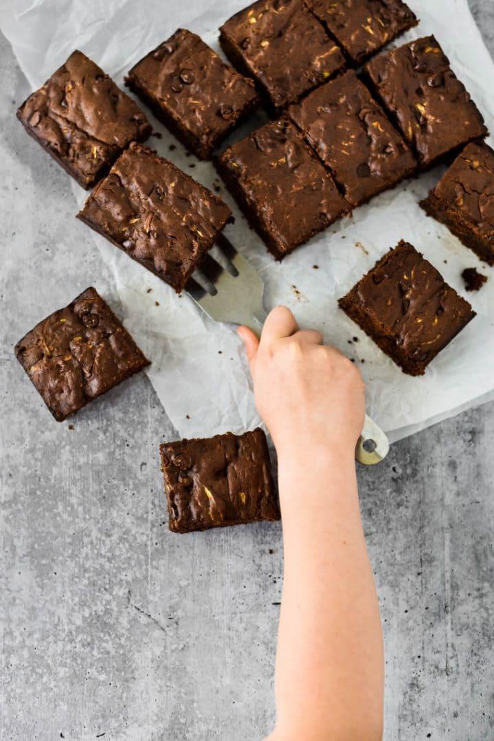 kids hand using spatula on zucchini brownies