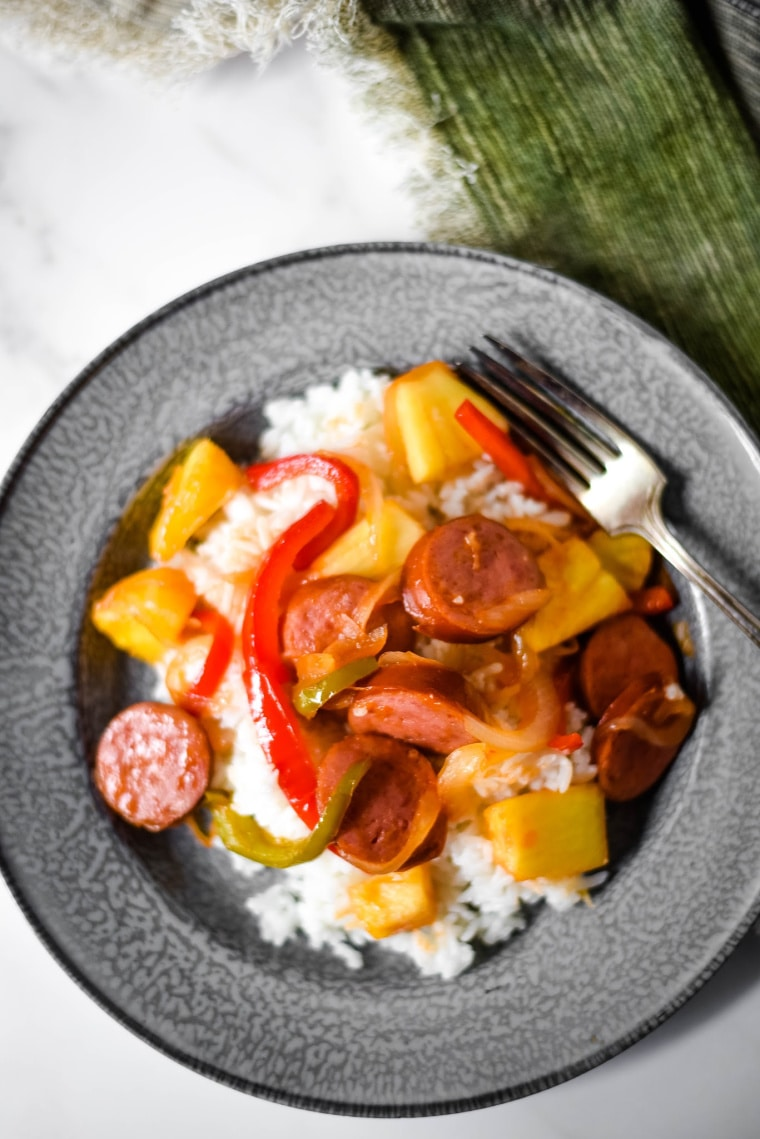 Sweet and Sour Kielbasa on blue grey plate with fork