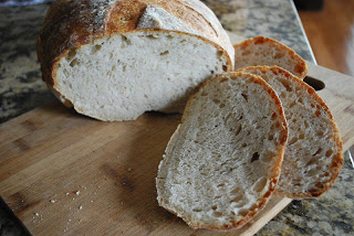 sourdough bread loaf with three cut slices in front of it