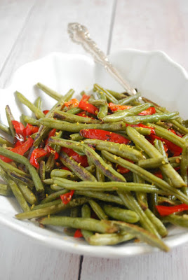 white serving bowl with green beans and red peppers topped with lemon zest