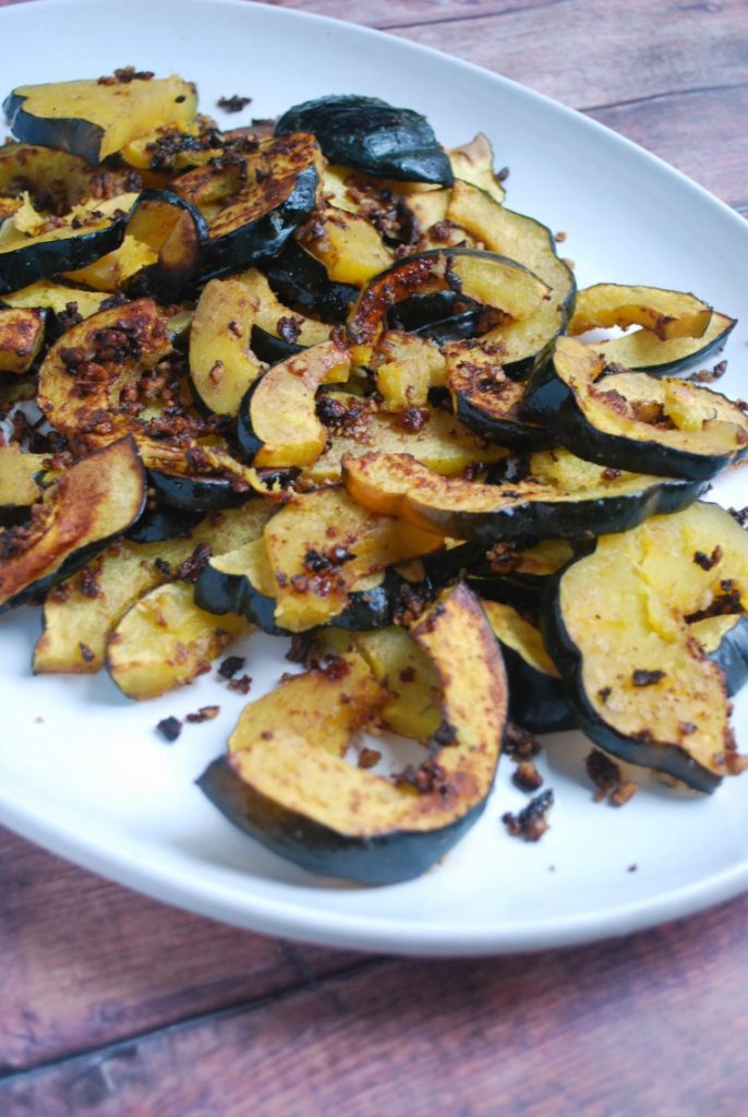 roasted squash on white platter with pecans