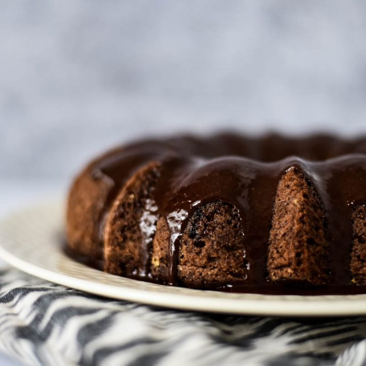 close up view of sourdough bundt cake with chocolate ganache drizzled on top