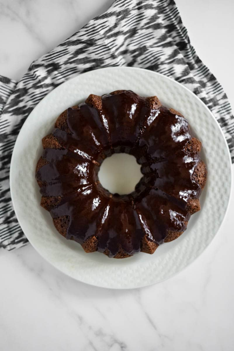 overhead view of chocolate sourdough bundt cake on white platter
