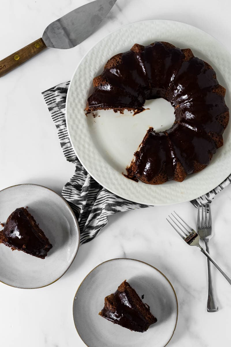overhead view of chocolate bundt cake with two slices beside on plates