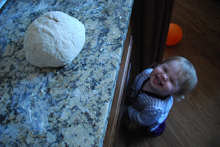 toddler looking at ball of san fransisco sourdough bread dough