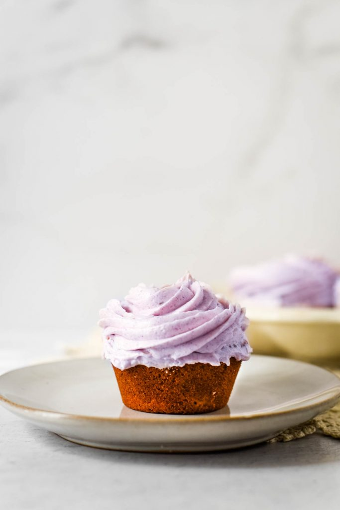 cupcake with purple frosting on small plate