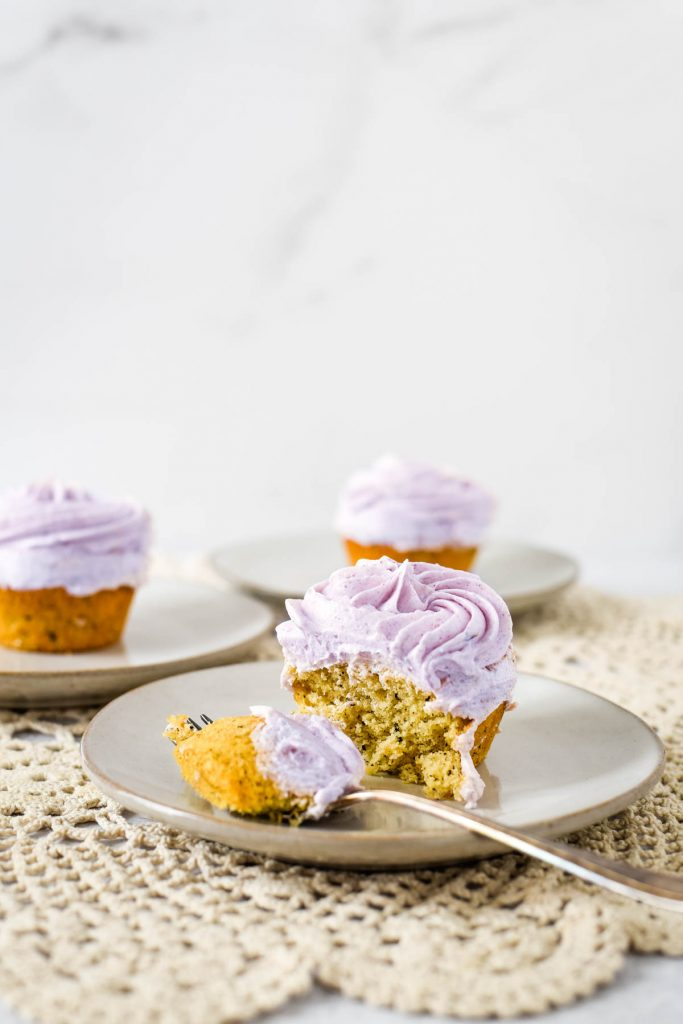 small plates with cupcakes with lavender buttercream and fork taking bite out