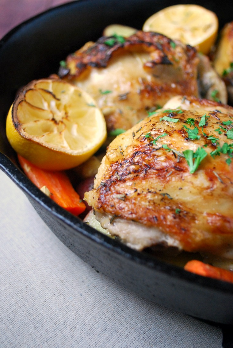 close up of roasted chicken thigh with carrots and lemon slices