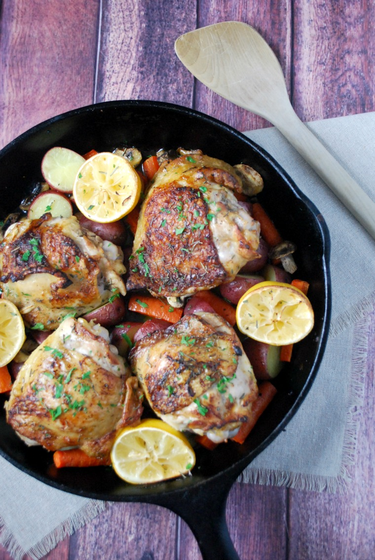 rosemary chicken with lemon and vegetables in a cast iron skillet