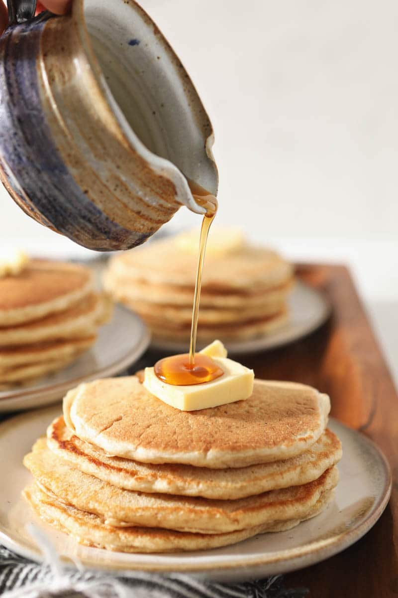 maple syrup being poured on sourdough pancakes