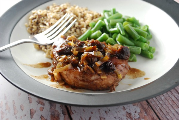 Braised Pork Chops with Cherry Sauce on plate with fork and rice and green beans