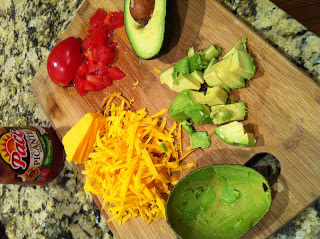 toppings for tacos: shredded cheese, tomatoes, avocado, and salsa