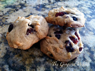 three sourdough cookies with walnuts, cranberries and chocolate chips sitting on marble counter