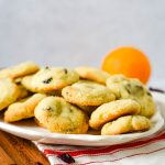 platter of cookies with oranges and cranberries beside