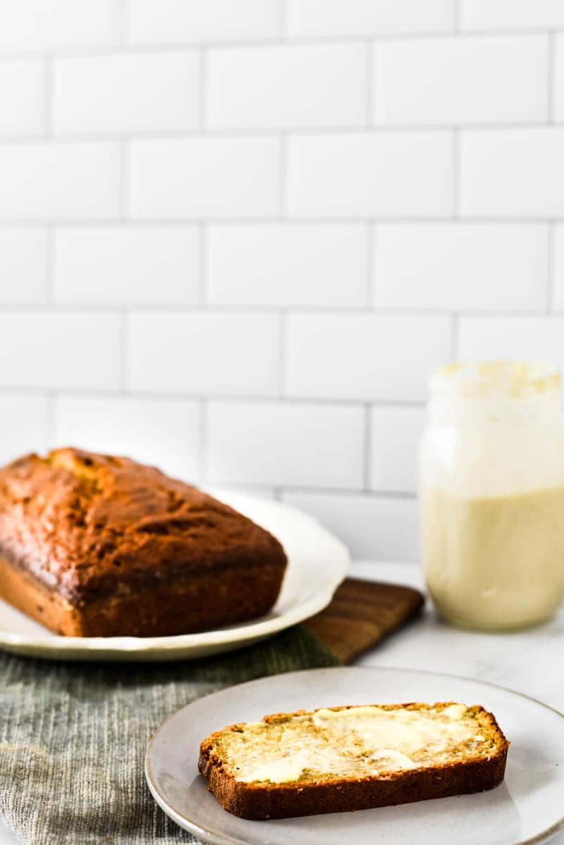 slice of banana bread with butter next to loaf and jar of sourdough stater