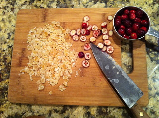 cutting board with chopped candied ginger and sliced cranberries