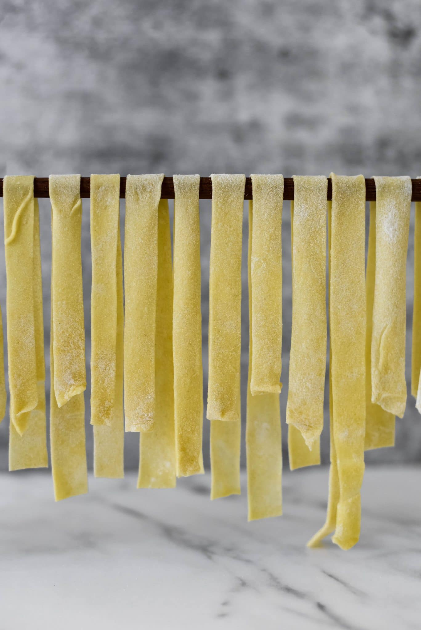 handmade sourdough pasta noodles hanging on wooden spoon