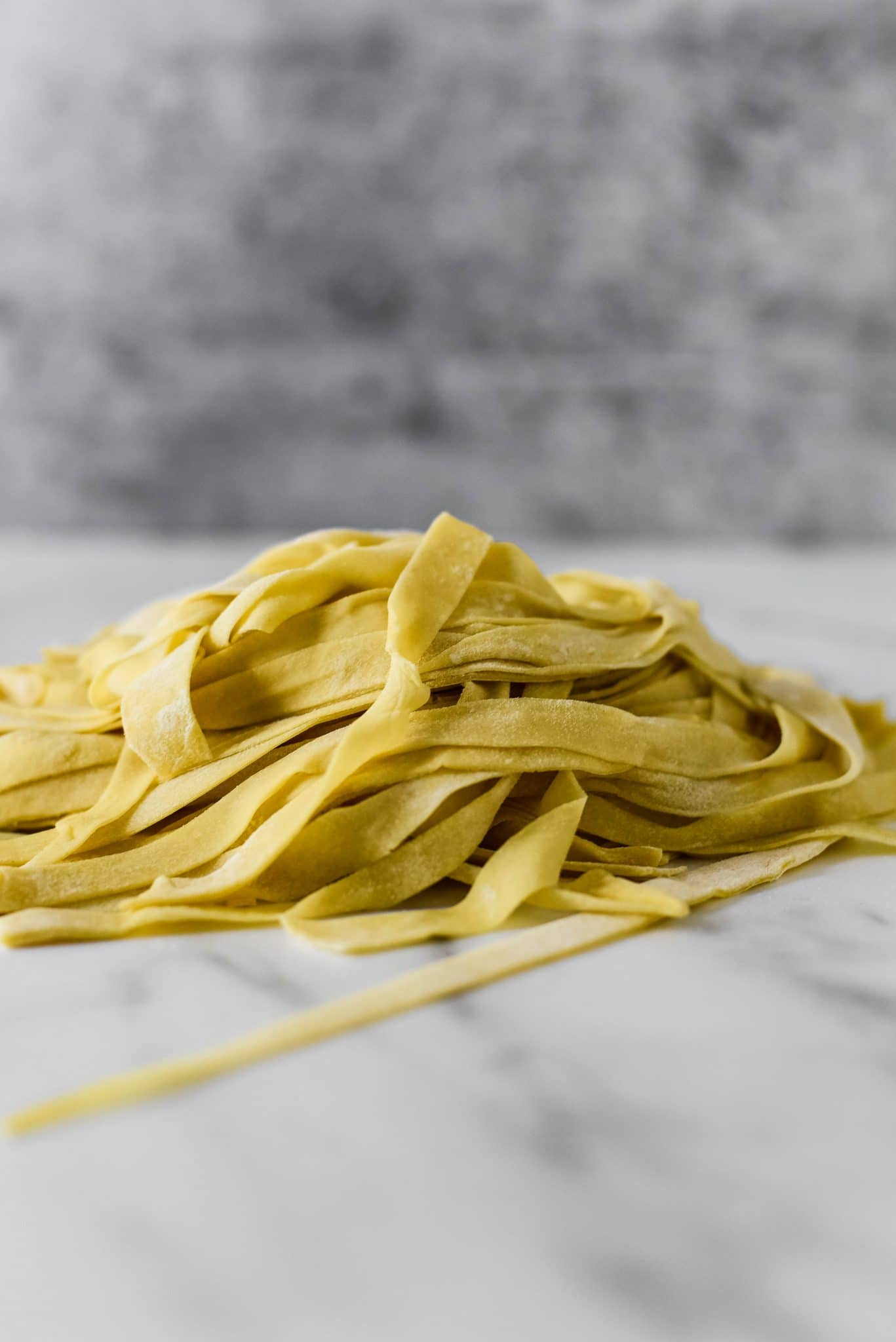 side view of pile of freshly made sourdough pasta noodles on marble
