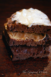 three slices of chocolate bread stacked, smeared with nutella, peanut butter, and cream cheese