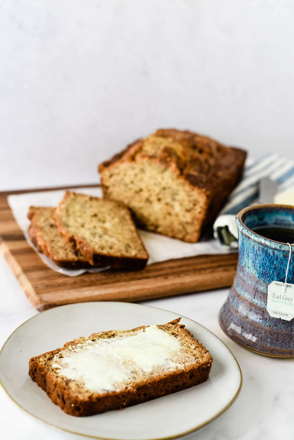 slice of tea cake on plate next to mug and loaf