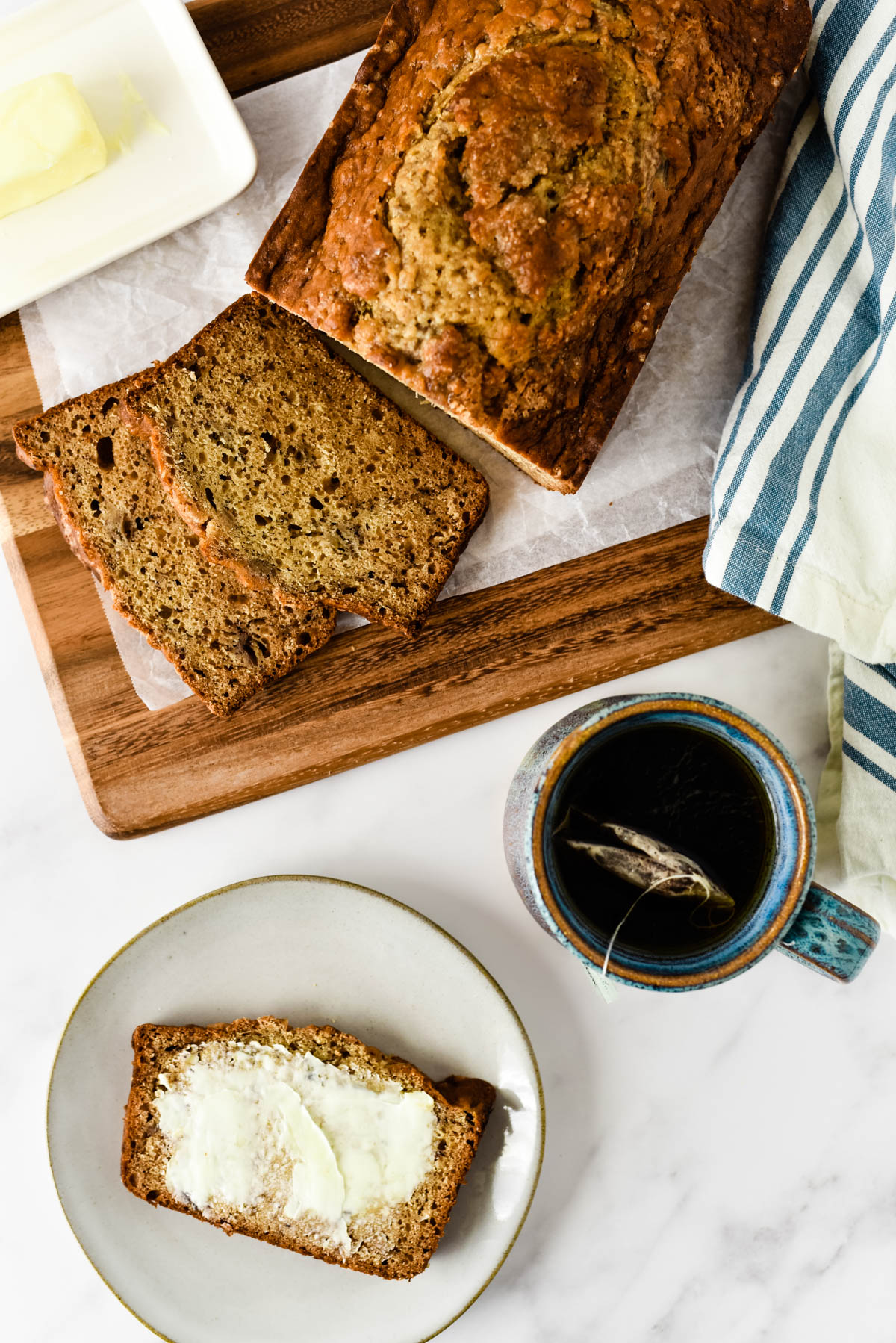 earl grey banana bread overhead on plate with loaf and tea beside