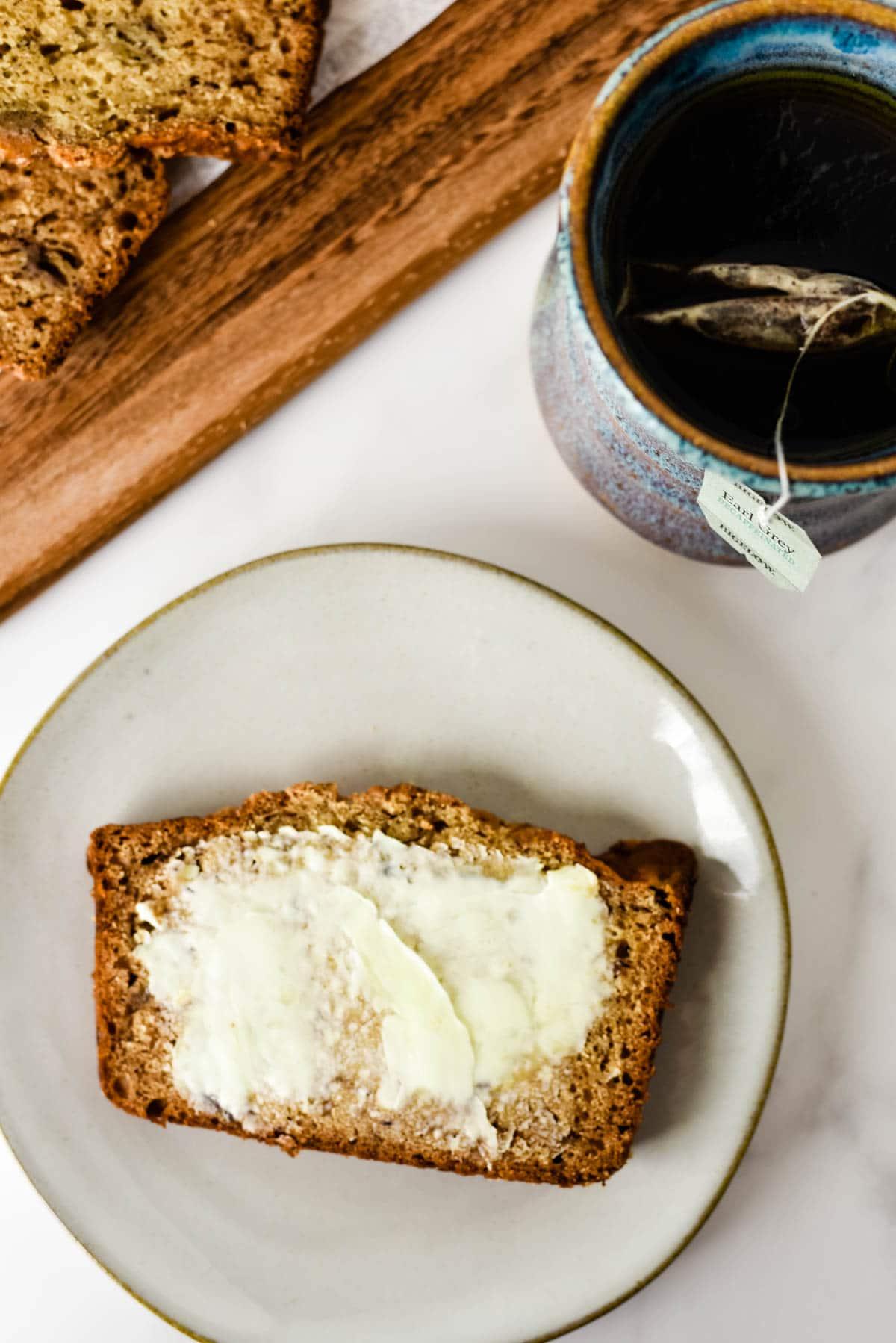 slice of earl grey banana on plate with butter and tea mug beside