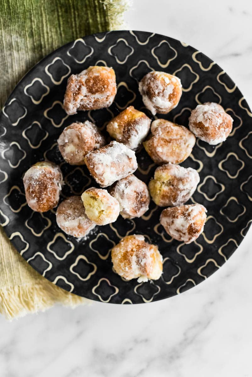 sourdough donut holes covered in powdered sugar on patterned plate