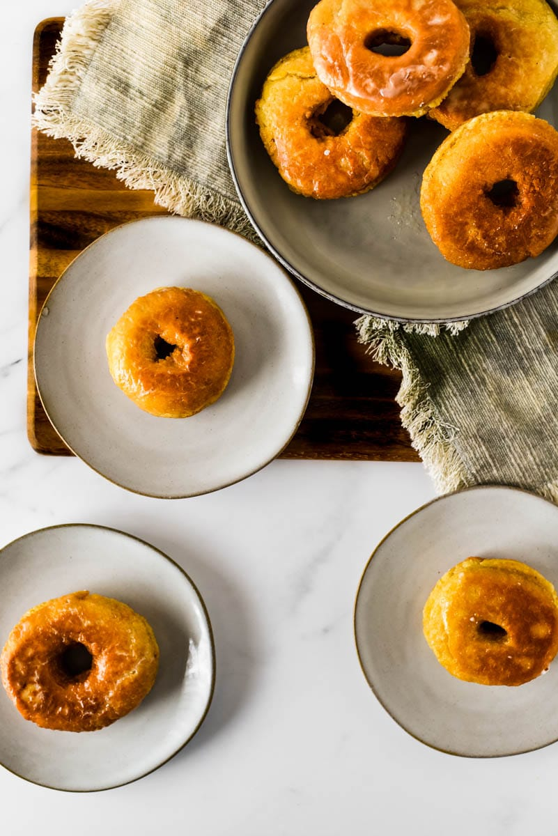 three sourdough donuts on small plates beside filled bowl
