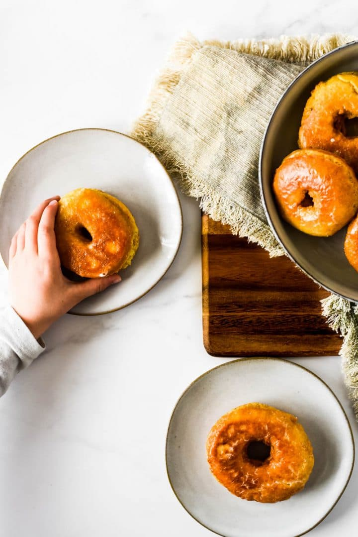 child's hand taking sourdough donut off of small plate