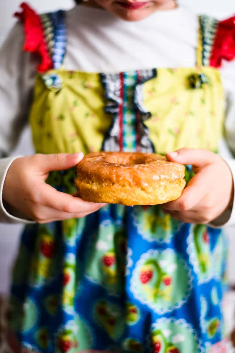 girl holding sourdough donut while wearing colorful dress