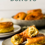 sourdough donut broken in half on plate, surrounded by more donuts. With text overlay of recipe title for pinterest