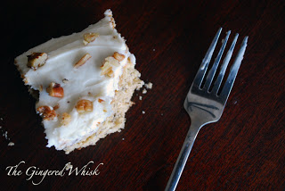 overview of banana cake with cream cheese frosting and pecans beside fork