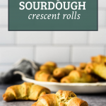 sourdough crescent rolls on cement with white platter behind. Includes text overlay of recipe title for pinterst