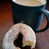 sourdough doughnut next to a cup of coffee