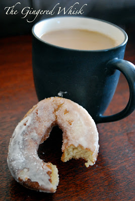 a close up of a sourdough donut with bite taken out of it next to cup of coffee